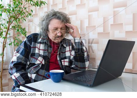 Elderly, Tired Man Working On A Laptop While Sitting At A Table At Home. A Gray-haired Man Suffering