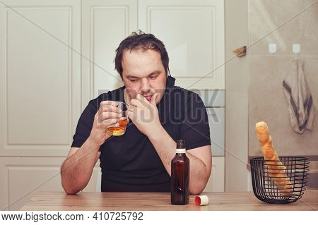 A Man In Thought Looks At A Glass Of Strong Alcohol. Alcoholism In Despair, Grief And Melancholy
