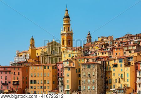 View of colorful houses and belfry of the Saint Michel Archange basilica under blue sky in Menton - small town on French Riviera.