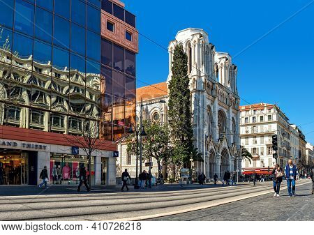 NICE, FRANCE - MARCH 26, 2016: People on Avenue Jean Medecin passing by Basilica of Notre-Dame and modern building in Nice - famous and one of the most visited cities on French Riviera.