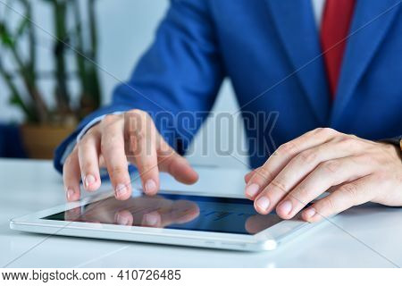 Businessman In Suit Using Digital Tablet Computer To Work With Financial Data And Stock Report. Busi