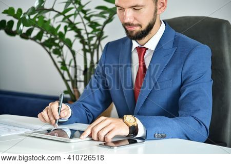 Businessman Sitting In Office And Using Digital Tablet Computer. Business And Financial Success Conc