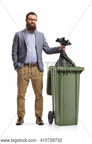 Full length portrait of a bearded man throwing a bin bag in a dustbin isolated on white background