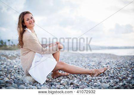 Young woman on the beach enjoying a warm summer evening