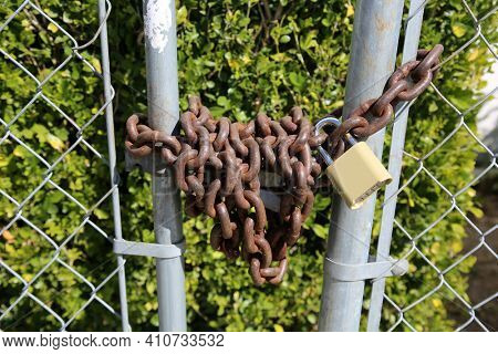 Lock and Chain. A rusty steel chain with a padlock securing a fence closed. Locks and Chains have been used for years to keep people in or out of various places.