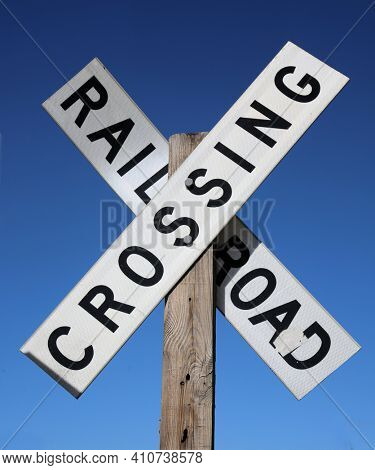 Rail Road Crossing Sign. A vintage Rail Road Crossing Sign against a Blue Sky background. Rail Road Crossings are throughout the united states of america.