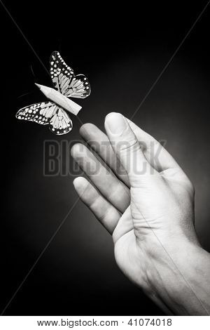 Male hand releasing a short pencil with butterfly wings, black and white image. Concept of creative writing.