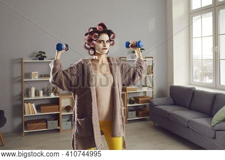 Funny Determined Woman In Curlers And Homewear Doing Fitness Exercise With Dumbbells