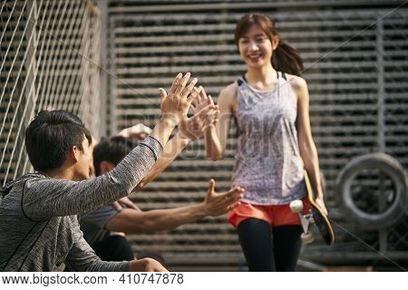 Young Asian Adult Woman Skateboarder Giving A Group Of Young Men Hi-five, Focus On Hand