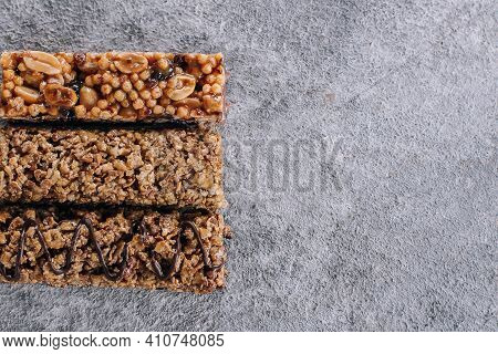 Granola Bar. Healthy Snack. Cereal Granola Bar With Nuts, Chocolate On Concrete Table Background. To