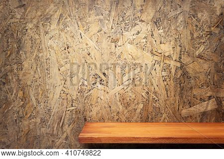 Wooden shelf or tabletop near chipboard wall background. Front view of shelf or table