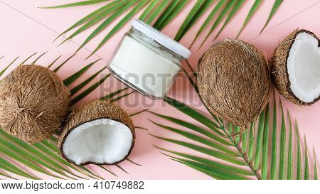 Jar Of Coconut Oil And Fresh Coconuts With Palm Leaves On Pink Background Top View. Coconut Butter F