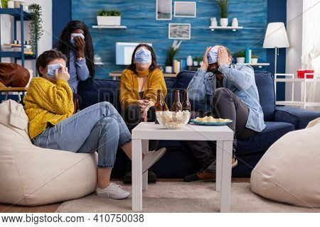 Multiethnic Friends Socialising Looking At Terrifying Movie On Tv Sitting On Sofa In Apartment Livin