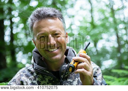 Smiling mature man walking and hiking in mountain forest and using radio set. Male spring outdoor portrait.