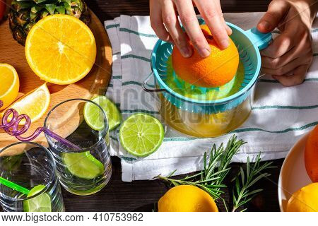 The Process Of Squeezing Juice From An Orange. Womens Hands Squeeze Orange Juice. Tropical Fruits On