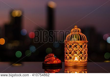 Golden Lantern And Dates Fruit With Dusk Sky And City Bokeh Light Background For The Muslim Feast Of
