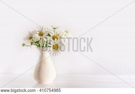 Bouquet Of Field Chamomile Flowers In Vase On White Background. Copy Space. Selective Focus.