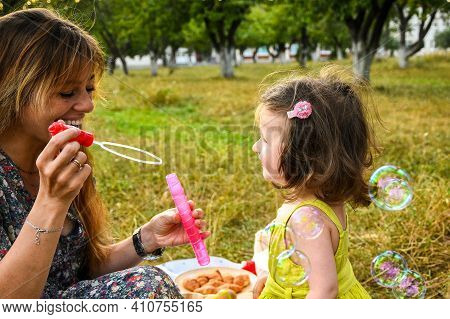 Parents Blowing Soap Bubbles To Child. Family Love First. Family Activity Leisure Outdoor In Autumn