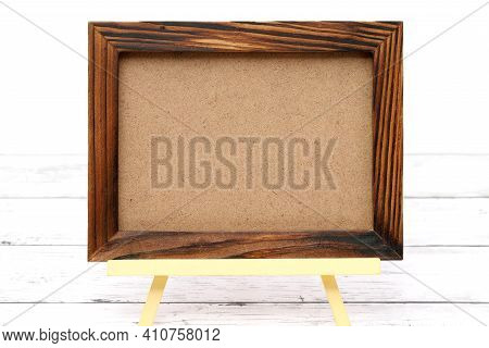 Old Wooden Picture Frame With Easel On Grunge White Table