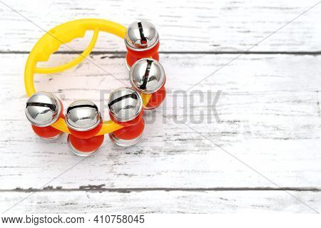 Colorful Jingle Bell On A White Wooden Table