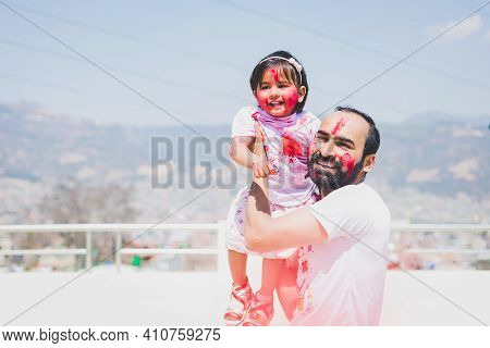 Father And Daughter Having Fun During Holi Purnima Or Holi Festival After Applying Colors To Each Ot