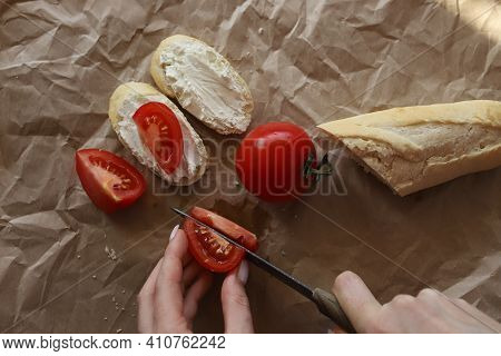 The Girl's Hands Are Cutting A Tomato On A Brown Background, Next To It Lies A Sliced Baguette, A Fr