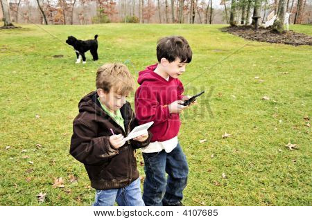 Two boys intensely playing Video games outdoors poster
