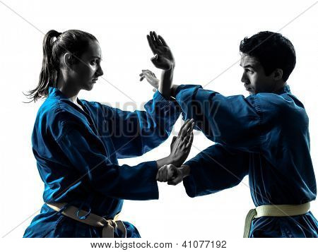 one  man woman couple exercising karate vietvodao martial arts in silhouette studio isolated on white background