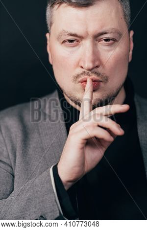 Portrait Of A Serious Business Man Showing Silence Gesture. Confidential Information, Silence Concep