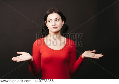 Confused Beautiful Woman Spreads Hands Sideways, Smirks Face, Feels Doubt While Making Choice. Girl