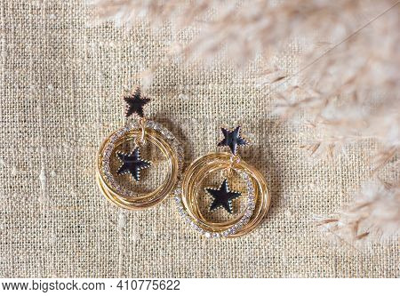 Gold Earrings Jewelry Jewelry On A Background Of Natural Canvas And Dry Reeds, Selective Focus, A Gi