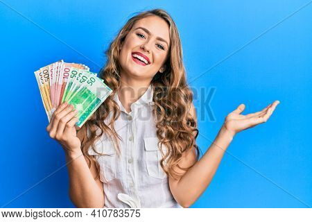 Young blonde girl holding norwegian krone banknotes celebrating achievement with happy smile and winner expression with raised hand