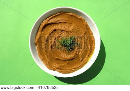 Arabic Cuisine - Peeled Fava Beans Mashed Plain In White Bowl On Green Background. Top View. Foul Mu
