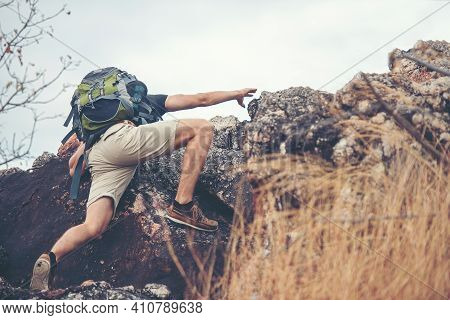 Hiker Man Climbing Natural Rocky Wall With Tropical Valley On The Background.   People Backpack Walk
