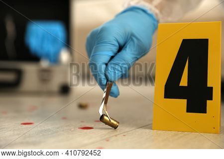 Investigator In Protective Gloves Working With Evidence Indoors, Closeup. Crime Scene