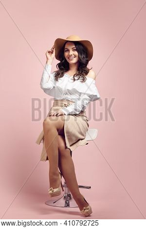 Cute Adult Girl With A Charming Smile Wearing A Beige Hat, White Shirt And Light Brown Skirt Sits On