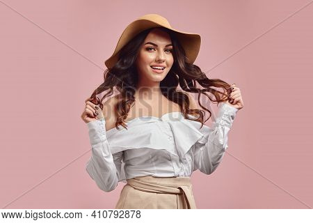 Glamour Studio Portrait Of Flirting Young Caucasian Woman With A Charming Smile Holding Her Brunette