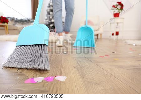 Woman Cleaning Messy Room After New Year Party, Focus On Broom