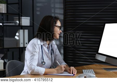 Doctor With Headset And Computer Consulting Patient Online In Office. Hotline Service