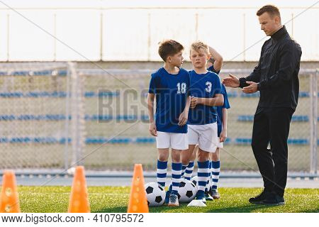 Soccer Coach Motivating Kids On Training. Young Coach With Kids In Soccer Team On Training Unit. Coa