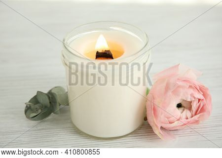 Candle With Burning Wooden Wick And Flower On White Table