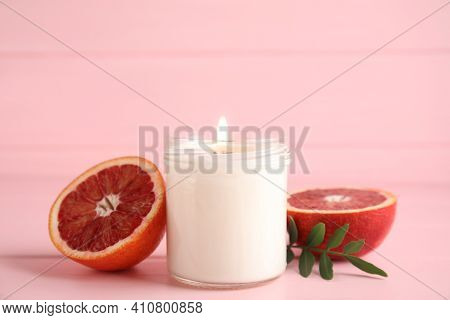 Scented Candle With Burning Wooden Wick And Cut Grapefruit On Pink Table