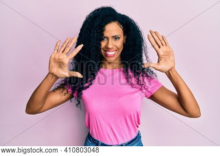 Middle age african american woman wearing casual clothes showing and pointing up with fingers number ten while smiling confident and happy.