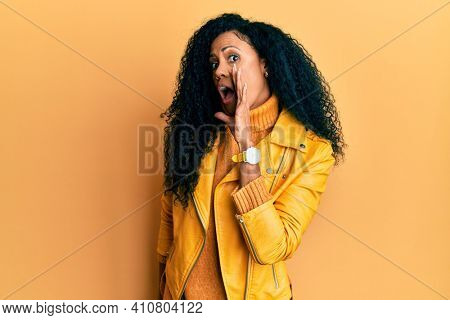 Middle age african american woman wearing wool winter sweater and leather jacket hand on mouth telling secret rumor, whispering malicious talk conversation