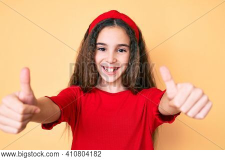 Cute hispanic child girl wearing casual clothes and diadem approving doing positive gesture with hand, thumbs up smiling and happy for success. winner gesture.