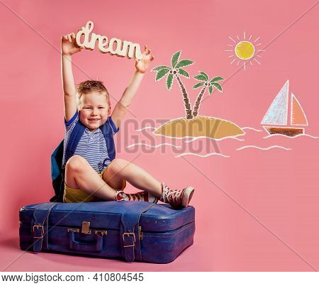 Happy Kid Dreams And Wish To Travel. Funny Child Boy With Dream Figure Sitting On The Suitcase. Trav
