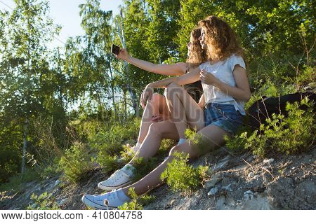 Two Girls On A Hike In The Mountains Take A Selfie