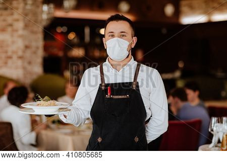Young Handsome Waiter In Black Apron And Medical Mask Holding Plate With Spaghetti Against Restauran