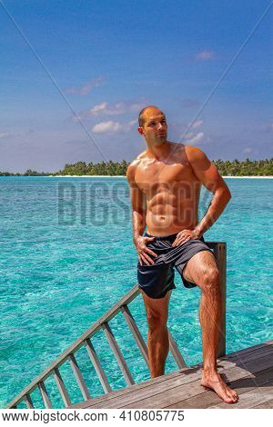 Sexy Man On Resort Beach In Summer. Handsome Male With Fit Body, Healthy Skin Sun Tan Tanning Near S