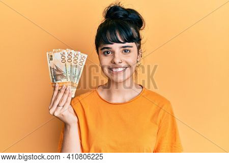Young hispanic girl holding norwegian krone banknotes looking positive and happy standing and smiling with a confident smile showing teeth